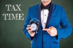 Man in suit holding and point to the clock Royalty Free Stock Images