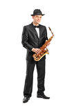 Man in a suit holding a saxophone. Full length portrait of a man in a suit holding a saxophone  on background Stock Photography