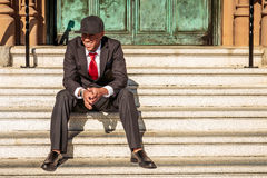 Man in suit holding sitting on steps. A young man in a suit with a red tie and hat sitting on steps Stock Photos