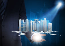 Man in suit holding skyscrapers in the hand Stock Photos