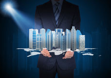Man in suit holding skyscrapers in the hand Stock Image
