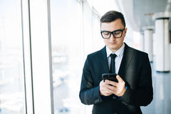 Man in suit holding smart phone and looking at it in office Royalty Free Stock Photo