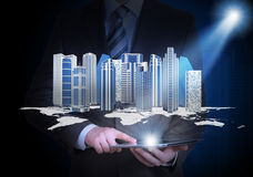 Man in suit holding tablet pc and skyscrapers Stock Photo