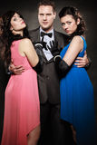 Man in suit holding two elegant women waist. Stock Image