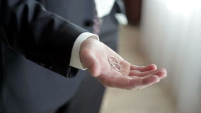 Man in a suit holding a two wedding rings.  stock video