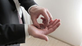 Man in a suit holding a two wedding rings stock video