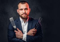 A man in a suit holds a Chef`s knife. An elegant bearded male in a suit holds a Chef`s knife over grey background royalty free stock photography