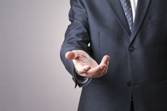 Man in a suit holds out an empty hand. On a gray background Royalty Free Stock Photos