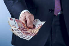 Man in a suit holds Russian rubles Stock Photos