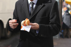 Man in a suit with a hotdog. A man eats a city hotdog in a fancy suit Royalty Free Stock Photo