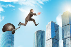 Man in suit with iron ballast hopping over city Royalty Free Stock Photos