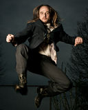 Man in Suit Jumping. A man with long hair in a retro style suit and boots jumping in mid-air Stock Images