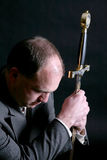 Man in a suit kneeling and gripping a sword Royalty Free Stock Photos