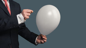 Man in Suit lets a Balloon burst with a needle Stock Image