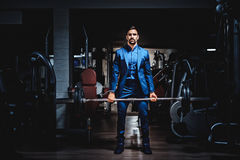 Man in suit lifting heavy weight. In the gym Royalty Free Stock Images