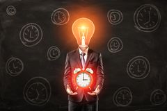 Man in suit with lightbulb instead head, levitating big red alarm clock above palms, standing against black wall with stock images