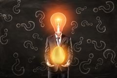 Man in suit with lightbulb instead head, levitating big shiny golden egg above palms, standing against black wall with royalty free stock photos