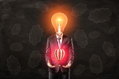 Man in suit with lightbulb instead head, levitating small hot-air balloon above his palms, standing against black wall stock illustration
