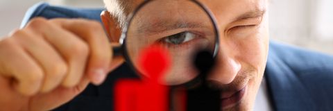 Man in suit look thru loupe on statuettes closeup Stock Photo