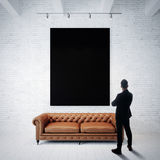 Man in  suit looking at black poster holding on the white brick wall. Classic sofa, wood floor. Vertical Stock Photography