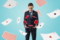 Man in suit looking down at poker chips floating in air with aces flying all around.