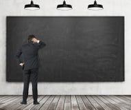 Man in suit looking at empty blackboard Stock Photo