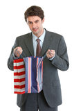 Man in suit looking into shopping bag Stock Image