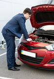 Man in suit looking under car bonnet Royalty Free Stock Image