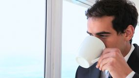 Man in a suit looks out the window then drinks Stock Photography