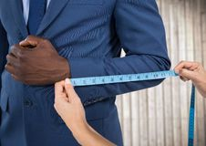 Man in suit mid section being measured against blurry wood panel Stock Images