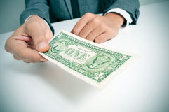 Man in suit offering a one US dollar bill Stock Image