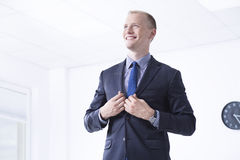 Man in suit in office area. Elegant man in suit standing in bright office area and smiling Stock Photo