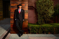 Man in suit in office complex. A young man in a suit with a red tie and hat standing in front of wood wall Royalty Free Stock Photo