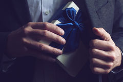 Man in suit opening a gift with blue ribbon Stock Photos