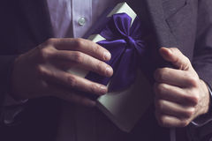 Man in suit opening a gift with purple ribbon Stock Image