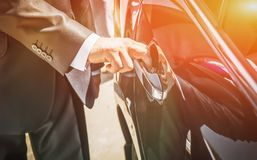 A man in a suit opens the door of a black car royalty free stock image