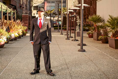 Man in suit in outdoor business park. A young man in a suit with a red tie and hat standing in front of alley Stock Photography