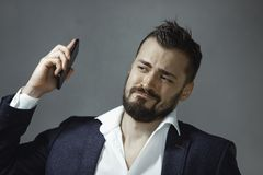 Man in Suit with Phone. Studio portrait of annoyed young Caucasian bearded man in suit white shirt getting disgusted because of his mobile phone loud annoying royalty free stock image