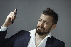 Man in Suit with Phone. Studio portrait of annoyed young Caucasian bearded man in suit white shirt getting disgusted because of his mobile phone loud annoying stock photography