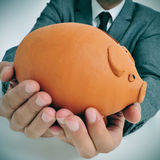 Man in suit with a piggy bank. A man wearing a suit holding a piggy bank in his hands Stock Image