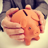 Man in suit with a piggy bank. A man wearing a suit sitting in a desk with a piggy bank in his hands Royalty Free Stock Photos