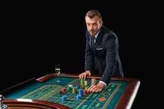 Man in suit playing roulette. addiction to gambling. Man in a suit playing roulette. addiction to gambling. In the hands of a glass. He bets chips stock photography