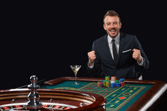 Man in suit playing roulette. addiction to gambling. stock image