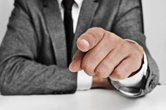 Man in suit pointing the finger. Man wearing a suit sitting in a table pointing the finger to the observer Royalty Free Stock Photography