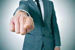 Man in suit pointing the finger. Man wearing a suit sitting in a table pointing the finger to the observer Stock Image