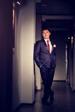 A man in a suit posing in the hallway of hotel in full length.  stock photography