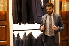 Man in suit posing  shop. Young Bearded Man in suit posing in shop and looking at camera Stock Images
