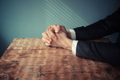 Man in suit praying at desk. Man in suit with his hands folded in prayer at a desk with light streaming through blinds Royalty Free Stock Images