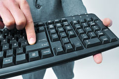 Man in suit pressing the enter key of a keyboard Royalty Free Stock Images