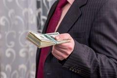 Man in suit propose dollar bunch close up.  stock photos